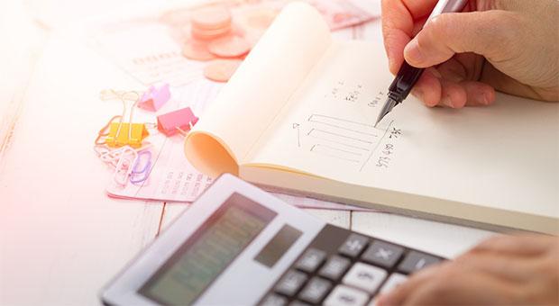 rose tinted calculator with pen and paper - geld besparen met je smartphone