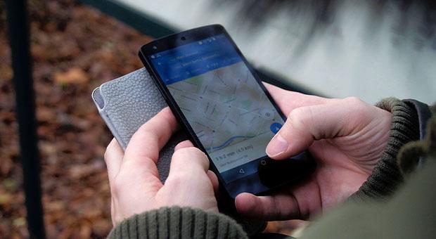 persoon - telefoon in hand - apps voor onderweg