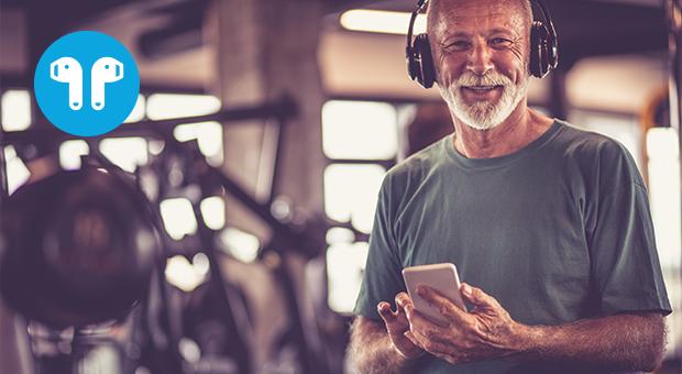 lachende senior man in sportschool koptelefoon
