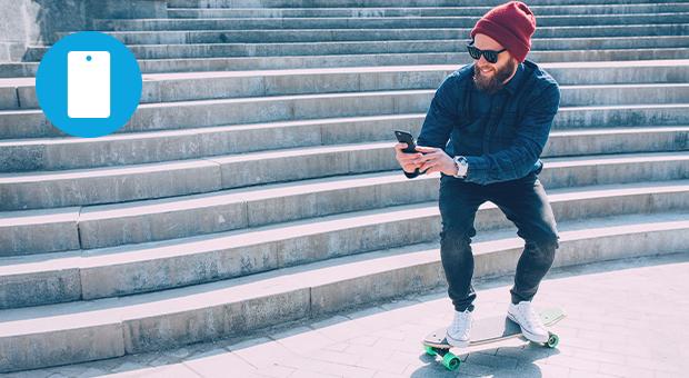 man skateboard smartphone buiten